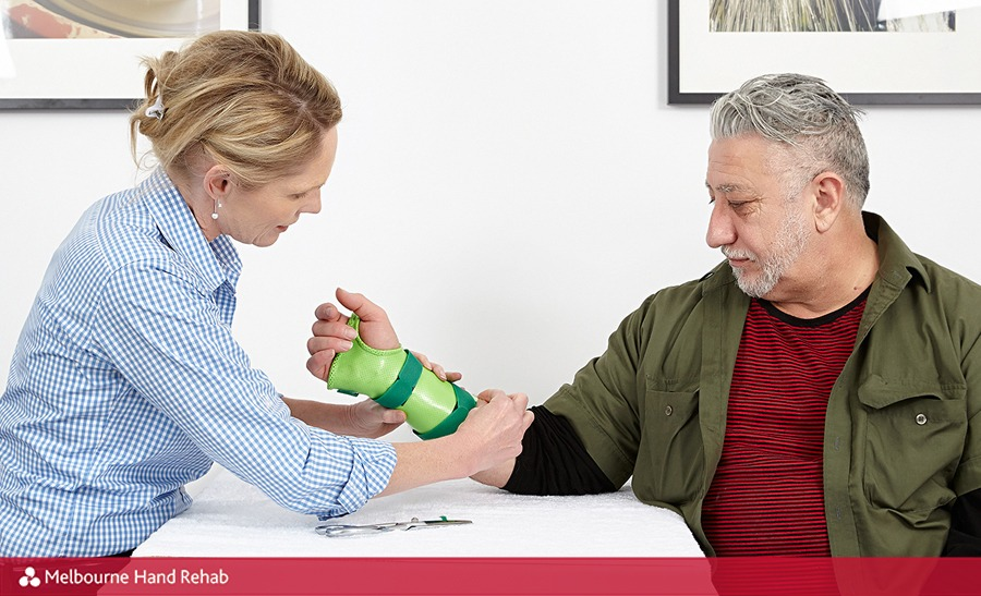 Melbourne Hand Rehab hand therapist Karen Fitt fitting a new hand splint onto male patient