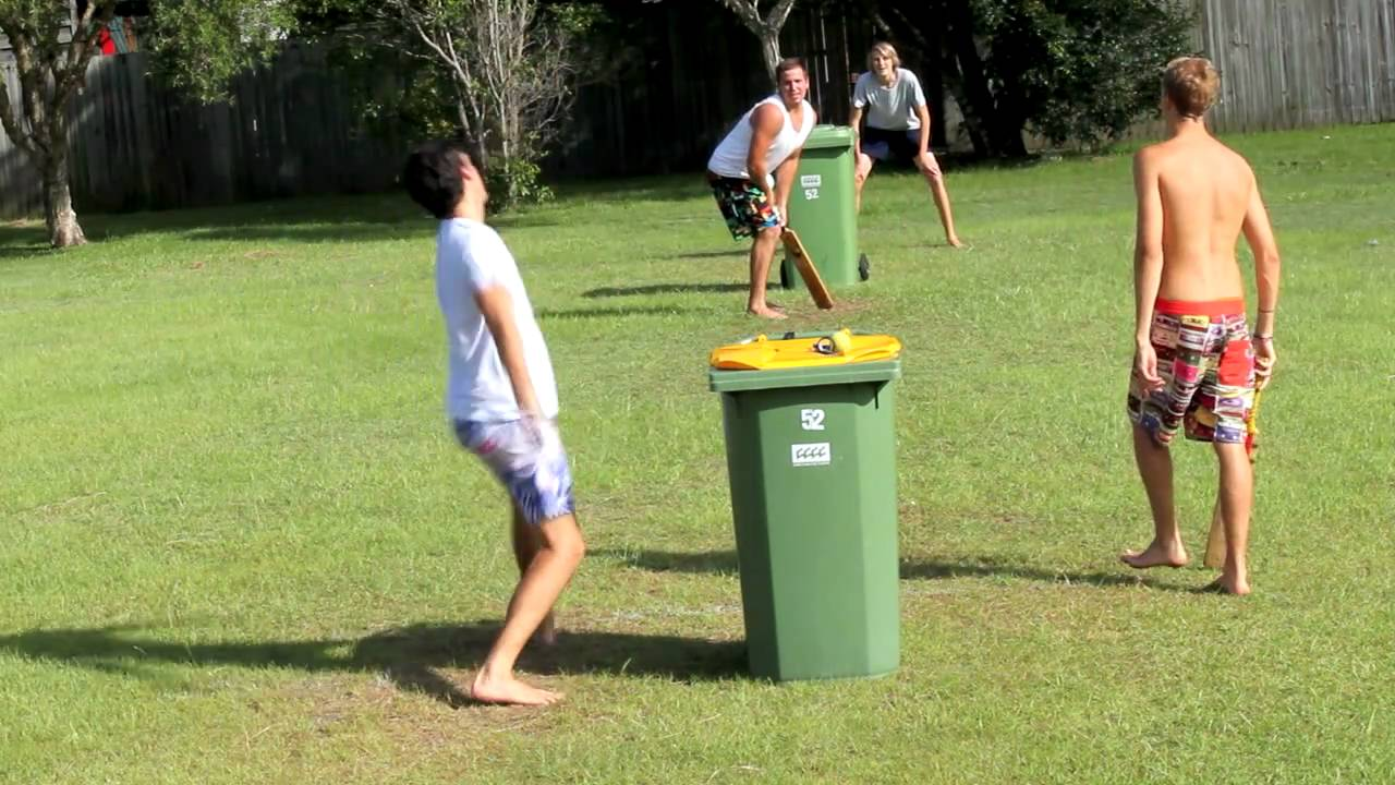 Kids playing backyard cricket with a wheelie bin as stumps