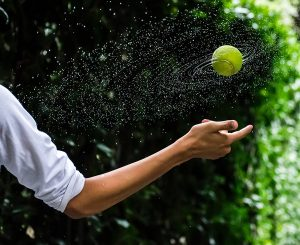 bowlers throws a wet tennis ball during a game of backyard cricket