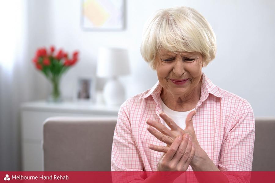Upset older woman suddenly feeling sharp arthritic pain in wrist